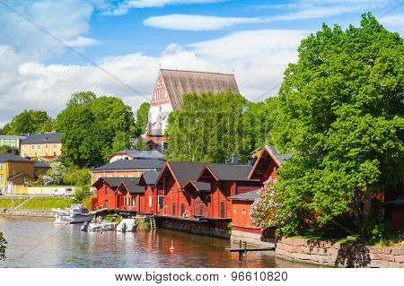 Finland. Old Red Wooden Houses And Trees