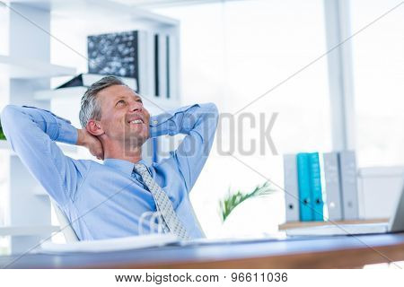 Businessman relaxing in swivel chair in office