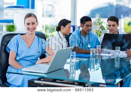 Happy doctor looking at camera while her colleagues looks at Xray in medical office