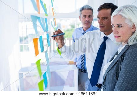 Businessman writing on post it with his colleagues in office