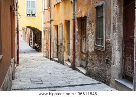 Old houses along narrow cobblestone street in medieval town Villefranche-sur-Mer on French Riviera, France.