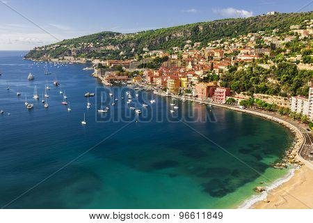 Aerial view of picturesque French Riviera mediterranean coast with medieval town Villefranche-sur-Mer, sandy beach and leisure boats anchored in harbor.
