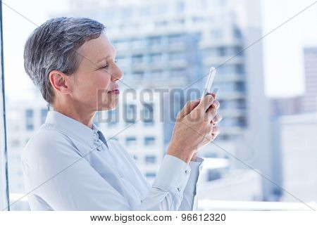 Businesswoman sending a text message in the office