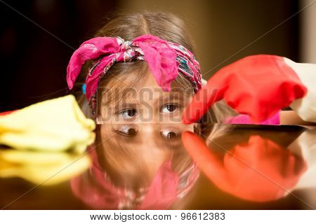 Closeup Of Girl Polishing And Cleaning Shiny Wooden Table