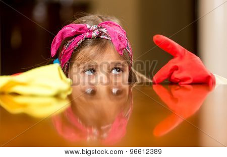 Portrait Of Girl Looking At Finger In Gloves Covered With Dust