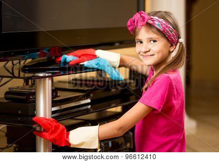 Portrait Of Smiling Girl Polishing Tv Table At Living Room