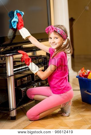 Portrait Of Cute Smiling Girl Cleaning Tv Screen