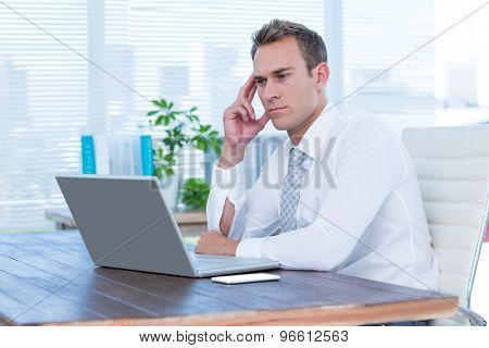 Frowning businessman looking at his laptop at office