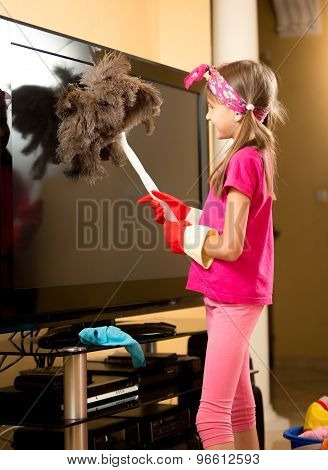 Girl In Rubber Gloves Cleaning Big Tv From Dust With Brush