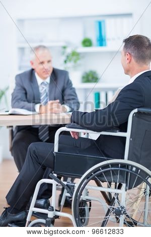 Businessman in wheelchair speaking with colleague in the office