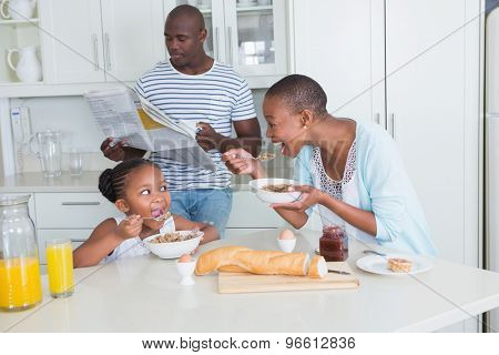 Happy family sitting and taking breakfast in the kitchen