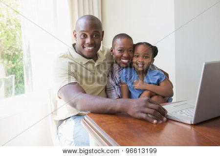 Happy smiling family using laptop at home