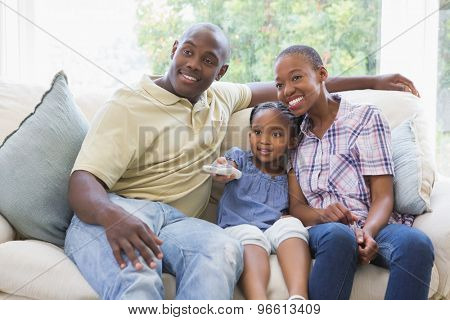 Happy smiling family watching television in living room