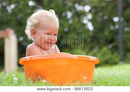 Cheerful Happy Cute Curly Baby Is Bathed In Orange Pelvis