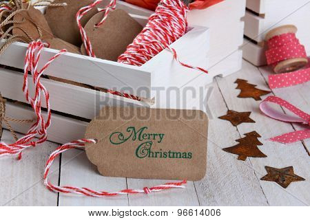 Closeup of a Christmas gift tag leaning on a wood box of wrapping supplies. Horizontal format on a rustic wood table.