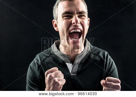 Excited rugby player yelling out on a black background
