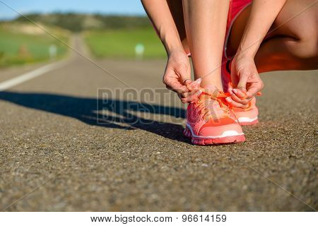 Woman Lacing Running Shoes Before Exercising