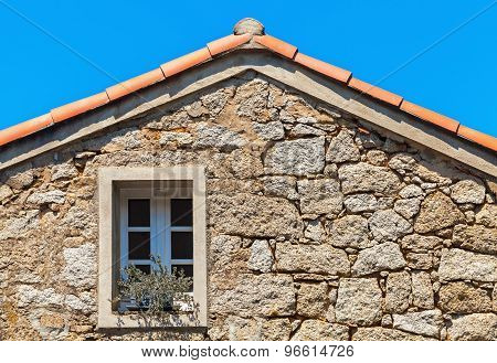 Stone Wall With Window Under Red Tile Roof