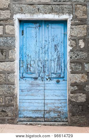 Old Blue Wooden Door In Gray Rural Stone Wall