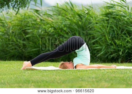 Young Woman Practicing Yoga Halasana Plow Pose
