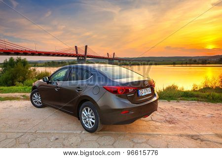 POLAND-SEPTEMBER 14, 2014: New Mazda 3 captured at sunset near Vistula river with HDR technique. Mazda 3 is a popular compact car manufactured in Japan by the Mazda Motor Corporation.