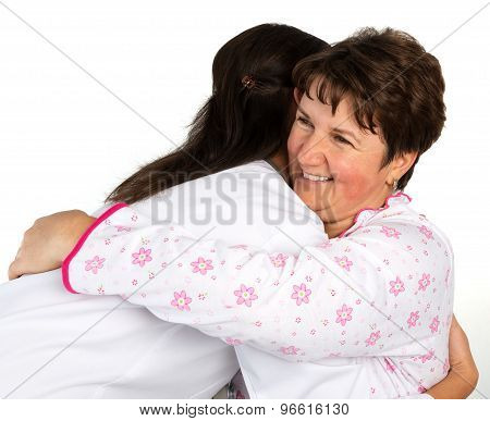 A Senior Woman And Nurse Hugging