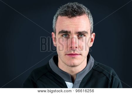 Portrait of a frowning rugby player on a black background