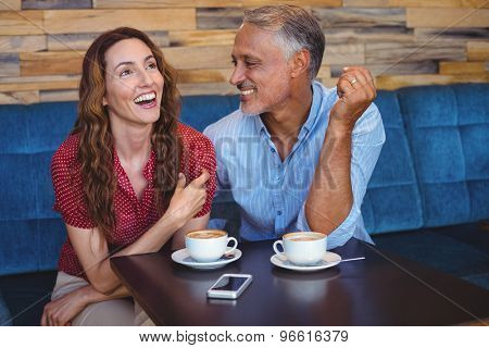 Cute couple laughing in the cafe