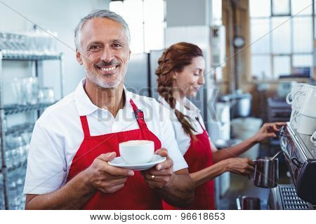 Happy barista smiling at camera and holding a cup of coffee with colleague behind at the cafe