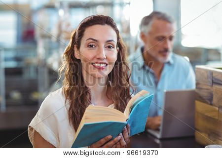 Pretty brunette looking at camera and holding book in the bakery store