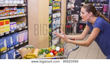 Surprised woman looking at product on shelf at supermarket