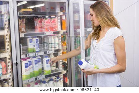 Pretty woman taking bottle of milk at supermarket