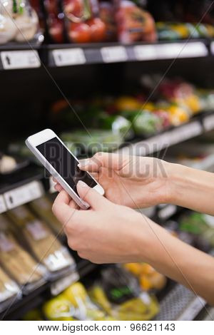 Woman buy products and using his smartphone at supermarket