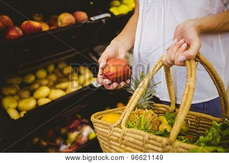 Smiling pretty blonde woman buying products at supermarket