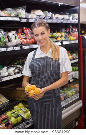 Pretty blonde holding apricots in the supermarket