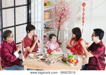 Chinese New Year festival, reunion dinner. Happy Asian Chinese multi generation family with red cheongsam dining at home.
