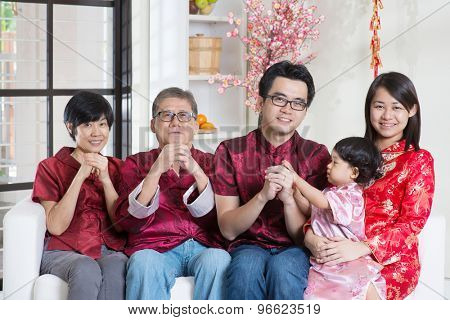 Celebrating Chinese new year. Happy Asian multi generations family in red cheongsam reunion and greeting at home.