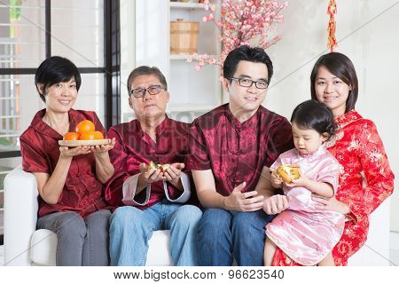 Celebrating Chinese new year. Happy Asian multi generations family in red cheongsam reunion at home.