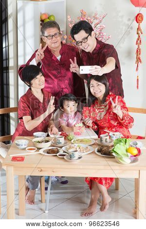 Celebrating Chinese New Year, taking selfie at reunion dinner. Happy Asian Chinese multi generation family with red cheongsam dining at home.
