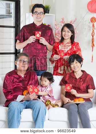 Celebrating Chinese new year. Happy Asian multi generations family in red cheongsam showing red packets while reunion at home.
