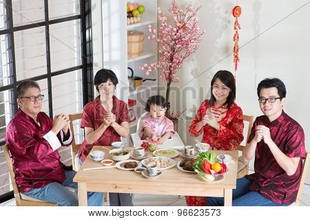 Happy Chinese New Year, reunion dinner. Happy Asian Chinese multi generation family with red cheongsam greeting while dining at home.