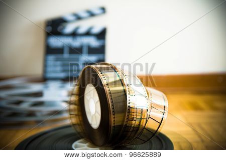 Cinema Film Reel And Out Of Focus Movie Clapper Board