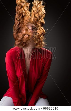 Sexy model posing waving her curly red hair