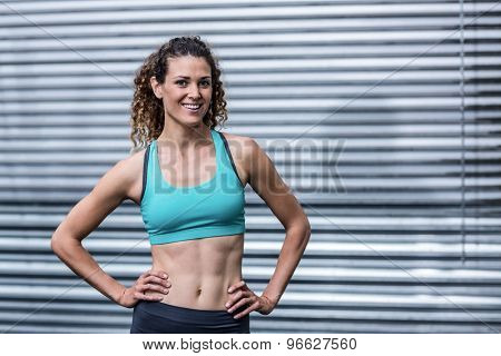 Portrait of a muscular woman with hands on hips