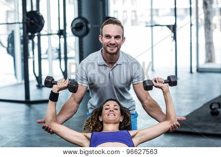 Trainer helping a muscular woman lifting dumbbells