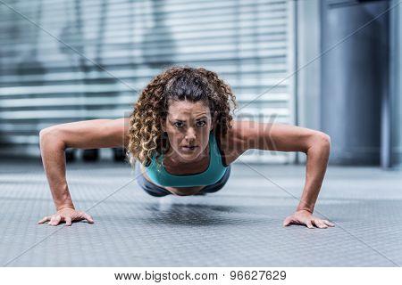 Portrait of an attentive muscular woman doing pushups