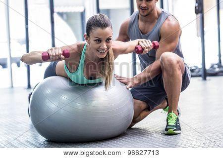 Muscular woman balancing while lifting dumbbells