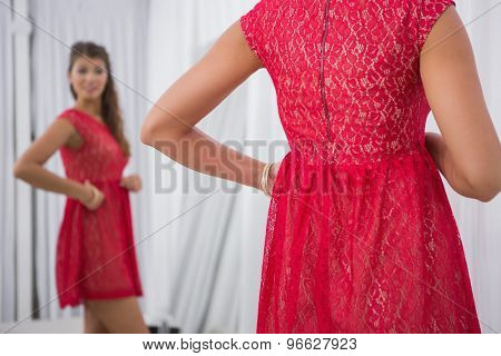 Smiling woman trying on a red dress at a boutique