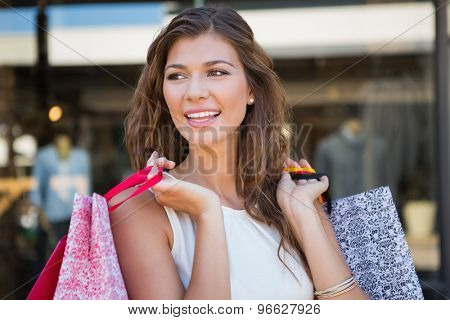 Smiling woman holding shopping bags at the shopping mall