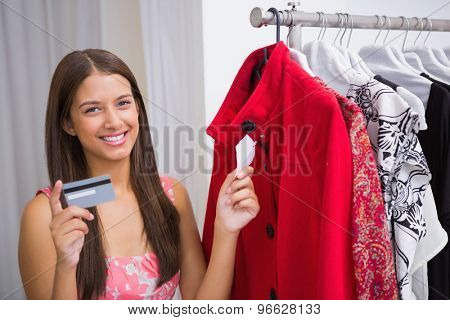 Portrait of smiling woman looking at red coat and holding credit card at a boutique